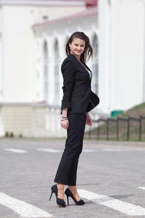 Brunette op naaldhakken buiten Jonge vrouw in zwart pak een wandeling langs het zebrapad Stockfoto
