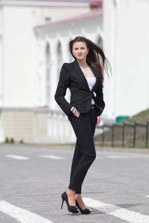 Brunette on stiletto heels outdoors  Young woman in black suit walking along the crosswalk photo