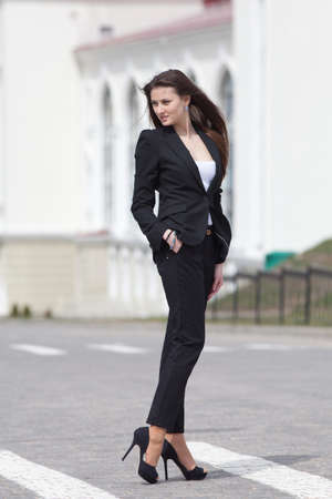 sexy business woman: Brunette on stiletto heels outdoors  Young woman in black suit walking along the crosswalk Stock Photo