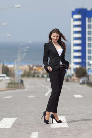 Brunette on stiletto heels outdoors  Young woman in black suit walking along the crosswalk photo