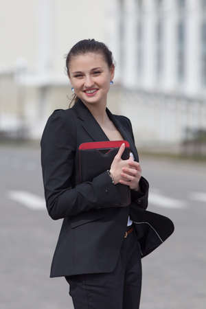 Brunette with tablet on open air  Young woman in black suit with tablet walking along the street photo