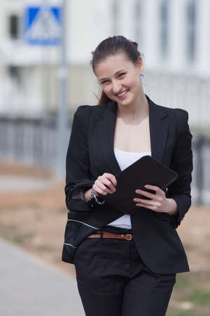 russian ethnicity caucasian: Brunette with tablet on open air  Young woman in black suit with tablet walking along the street Stock Photo