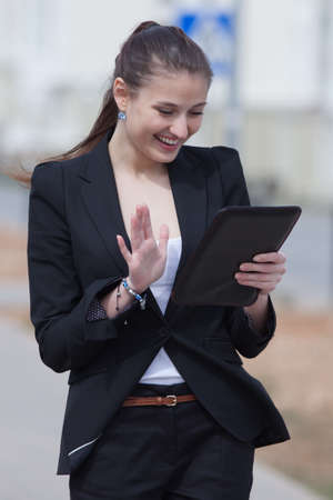 Brunette with tablet on open air  Young woman in black suit looking at screen of tablet smiling outdoors photo
