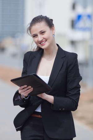 Brunette met tablet op de open lucht Jonge vrouw in zwart pak met een tablet-computer in haar handen te kijken naar de camera lacht