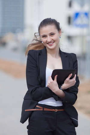 Brunette with tablet on open air  Young woman in black suit with tablet computer in her hands looking at camera smiling Stock Photo - 13301059