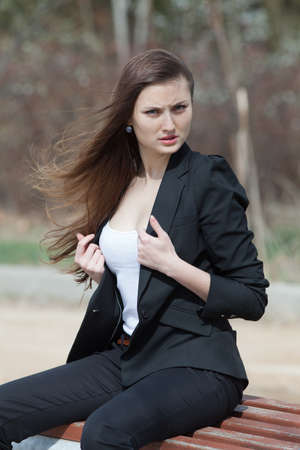 russian ethnicity caucasian: Young woman in the park  Dark hair girl in black suit sitting on bench in park looking at camera