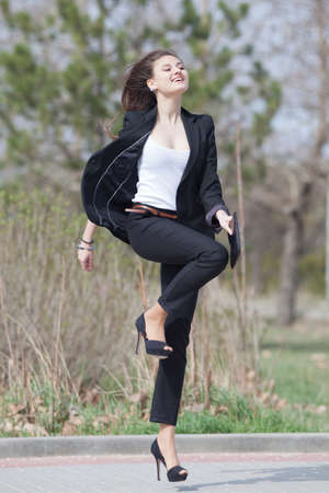 Brunette on stiletto heels in the park  Happy young woman in black suit runs along the park photo