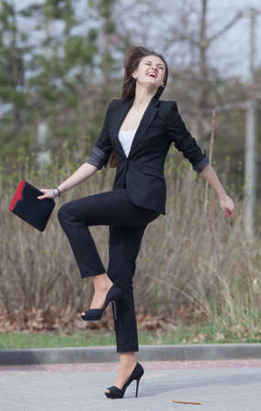 Brunette on stiletto heels in the park  Happy young woman in black suit with tablet computer in her hands runs along the park photo