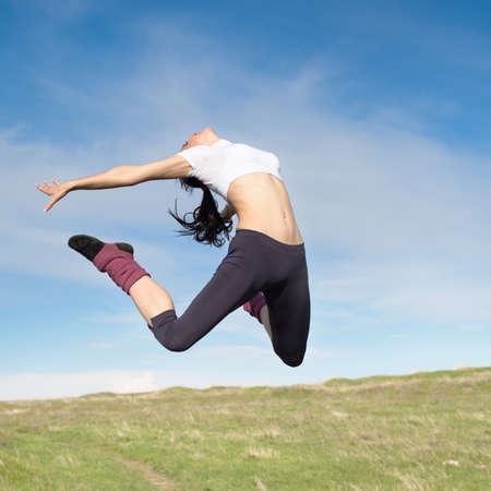 salto largo: Mujer joven atractiva saltando en saltos de aire Morena abiertos en el fondo del cielo