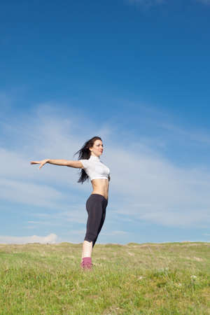 Girl dancing on background of sky  Attractive brunette posing on field photo