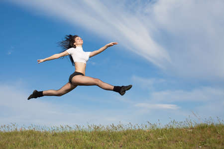 Attractive young woman jumping on open air  Brunette jumps on background of sky photo