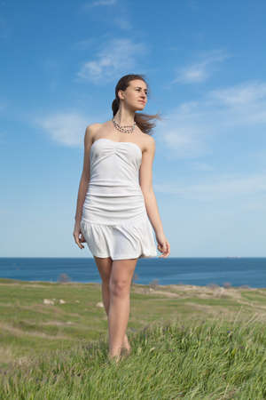Girl in white on open air  Attractive young woman in white dress walking along field Stock Photo - 13467981