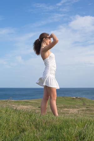 Girl in white on open air  Attractive young woman in white dress looks into the distance