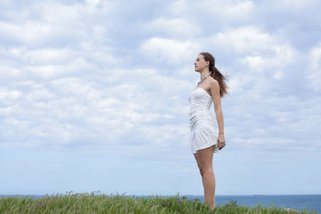 russian ethnicity caucasian: Girl in white on open air  Attractive young woman in white dress posing on background of sky