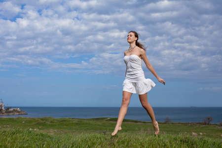 Meisje in wit op de open lucht Aantrekkelijke jonge vrouw in witte jurk loopt langs veld Stockfoto