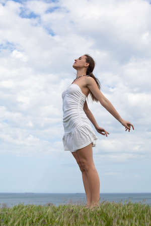Girl in white on open air  Attractive young woman in white dress posing on background of sky photo