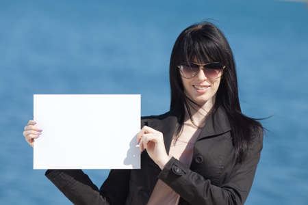 well dressed  holding: Attractive brunette in black on background of sea
