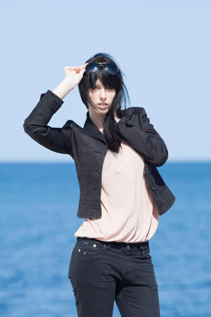 Portrait of attractive brunette in black on background of sea Stock Photo - 13646510