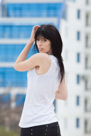Portrait of dark haired girl in white singlet looking at camera over her shoulder photo