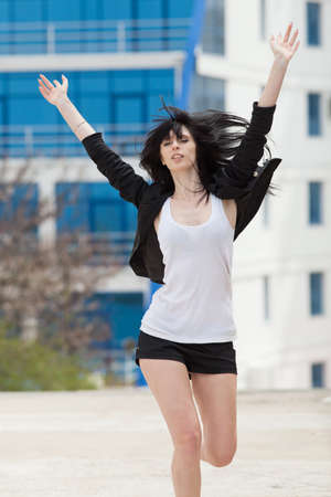 russian ethnicity caucasian:   Young woman in black shorts and jacket running along the street with arms raised