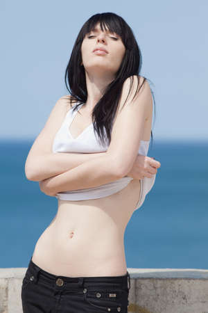 russian ethnicity caucasian:  Young woman in white singlet undressing with background of sea