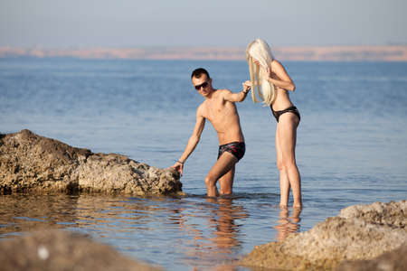 blondie: Attractive couple at the sea  Young man and woman in swimwear on wild rocky seashore Stock Photo