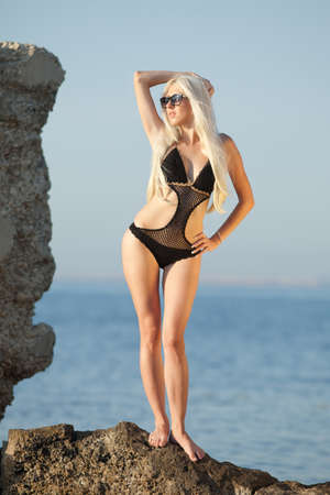 blondie: Girl at the sea  Attractive young blond woman in swimsuit posing on background of sea