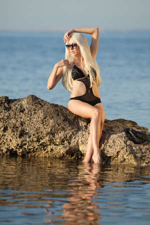 Girl at the sea  Attractive young blond woman in swimsuit posing on background of sea Stock Photo - 13764059