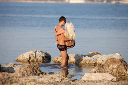 Attractive couple at the sea  Young man carrying blondie walking along wild rocky seashore Banque d'images