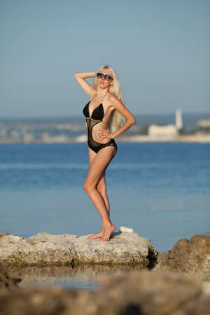 Girl at the sea  Attractive young blond woman in swimsuit posing at the sea photo