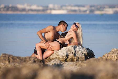 affectionate action: Atractiva pareja en el hombre de mar joven y una mujer en traje de ba�o coqueteando en la roca natural en el mar