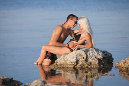 Attractive couple at the sea  Young man and woman in swimwear flirting on wild rock at the sea