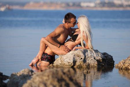 affectionate action: Atractiva pareja en el hombre de mar joven y una mujer en traje de ba�o coqueteando y bes�ndose en la roca natural en el mar Foto de archivo