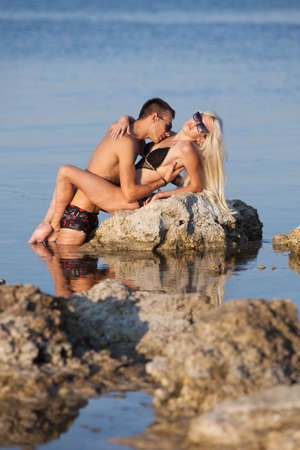 Attractive couple at the sea  Young man and woman in swimwear flirting and kissing on wild rock at the sea photo