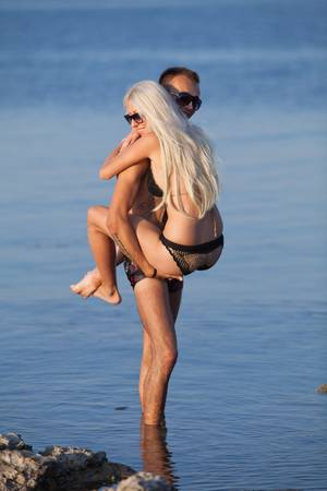 blondie: Attractive couple at the sea  Young man carrying blondie standing in water