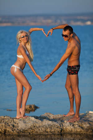 Attractive couple at the sea  Young man and woman in sunglasses posing a heart with their hands on rocky coast photo