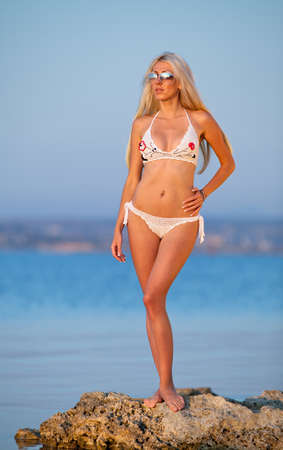 Girl at the sea  Attractive young blond woman in white swimsuit posing at the sea photo