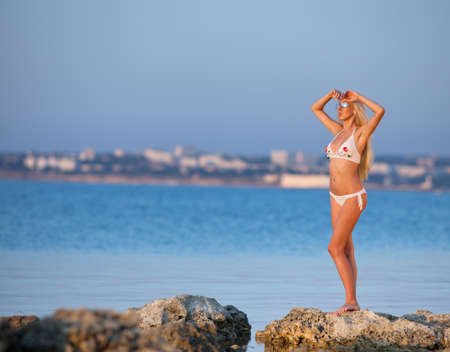 Girl at the sea  Attractive young blond woman in swimsuit posing on wild rocky seashore photo
