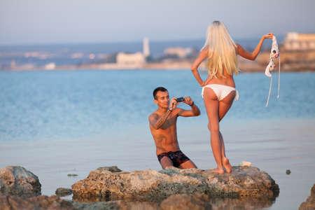 homme nu: Attractive couple sur la plage de l'homme jeune est la prise de photos de sa petite amie Banque d'images
