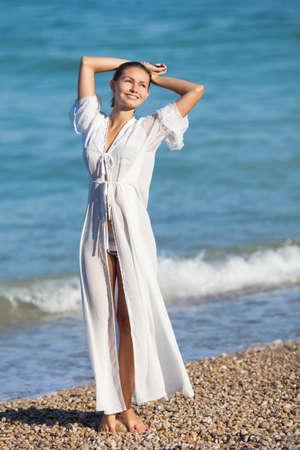 Aantrekkelijk meisje in het wit aan de zee Jonge vrouw die zich op zee Stockfoto