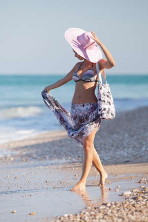 Attractive girl in hat at the sea  Young woman walking along the seashore photo