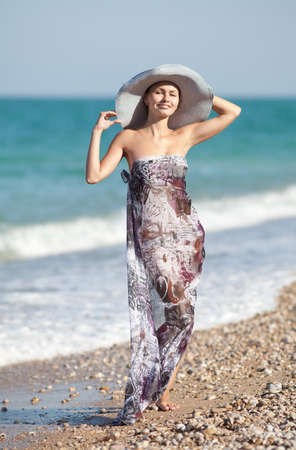 Attractive girl in hat at the sea  Young woman posing on seashore photo