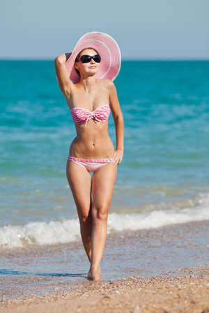 Attractive girl in swimwear at the sea  Young woman posing on seashore
