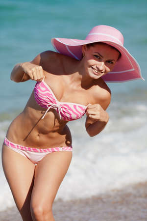 color photography: Attractive girl in swimwear at the sea  Young woman posing on seashore