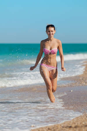 Attractive girl in swimwear at the sea  Young woman running along the seashore photo