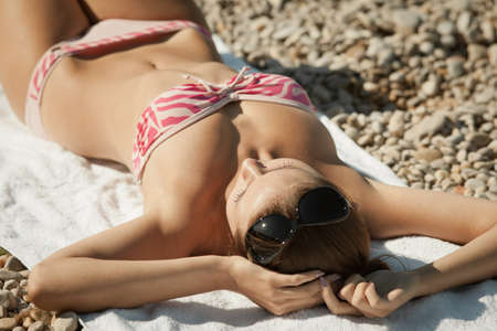 Attractive girl in swimwear lies on sand  Young woman tans photo