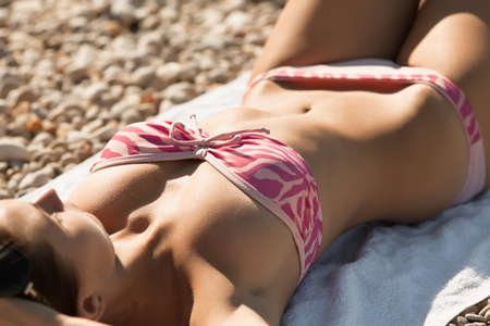 Attractive girl in swimwear lies on sand  Young woman tans