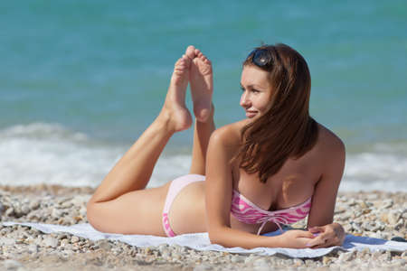 Attractive girl in swimwear lying on front on sand  Young woman tans photo