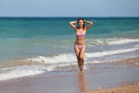 Attractive girl in swimwear with arms raised at the sea  Young woman walking along the seashore photo