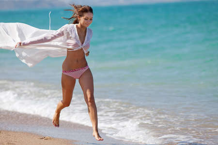 Attractive girl in swimwear at the sea  Young woman running along the seashore Stock Photo - 13957778